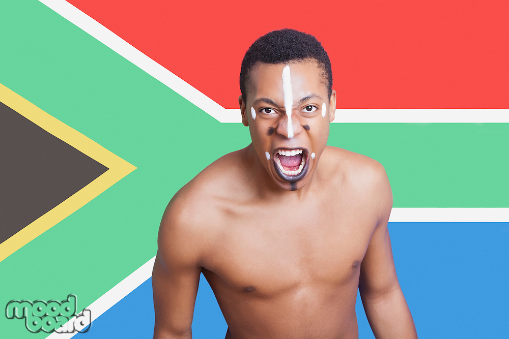 Portrait of aggressive mixed race man against South African flag