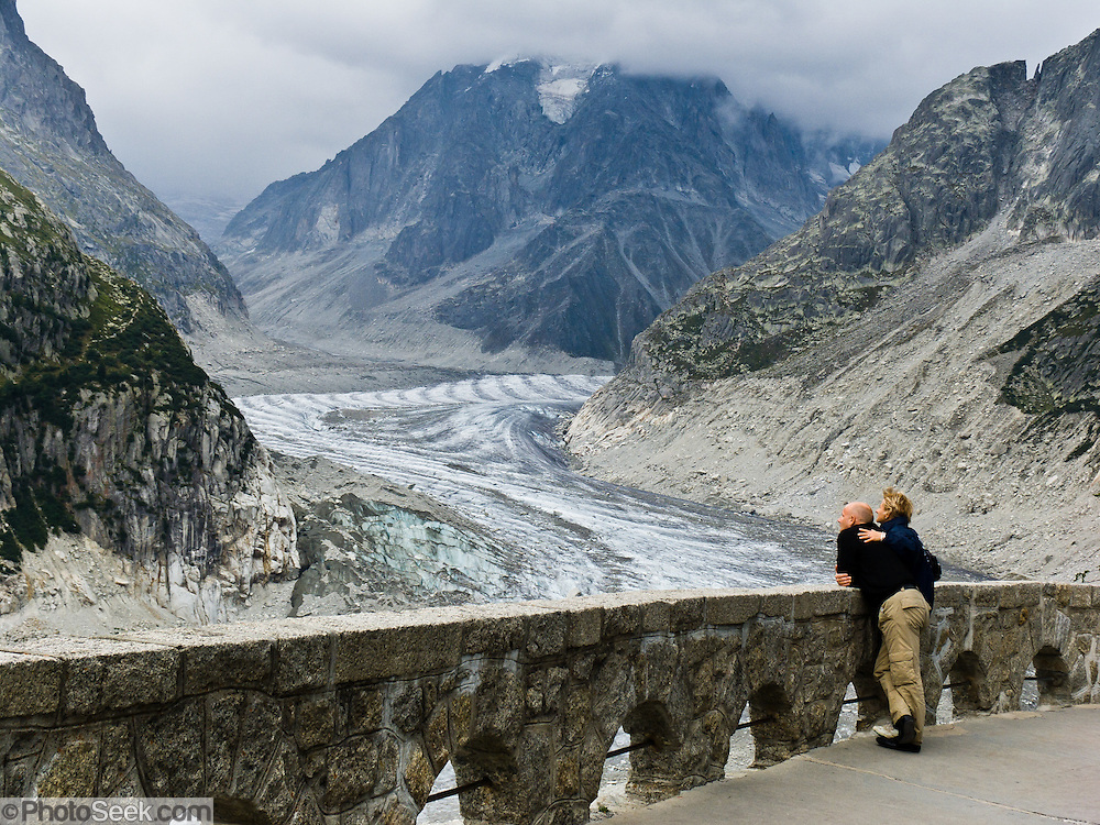 A couple of people hug and admire the Mer de Glace (Sea of Ice), a classic glacier easily accessible via cog railway or day hike from Chamonix, France, Europe. At 7 kilometers (4.3 miles) long, it is the longest glacier in France. It was once easily visible from Chamonix, but has been shrinking and is now barely visible from below. In the 1700s and 1800s, the glacier descended way down to the hamlet of Les Bois, where it was formerly known as Glacier des Bois.