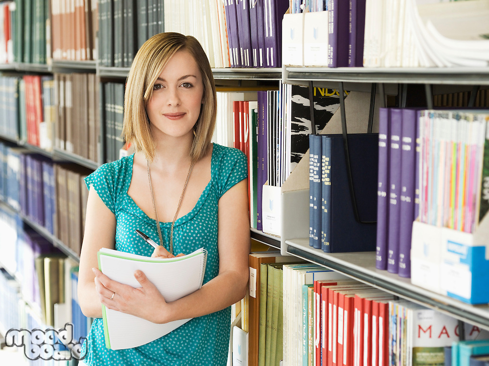 Young woman standing by bookshelf in library taking notes