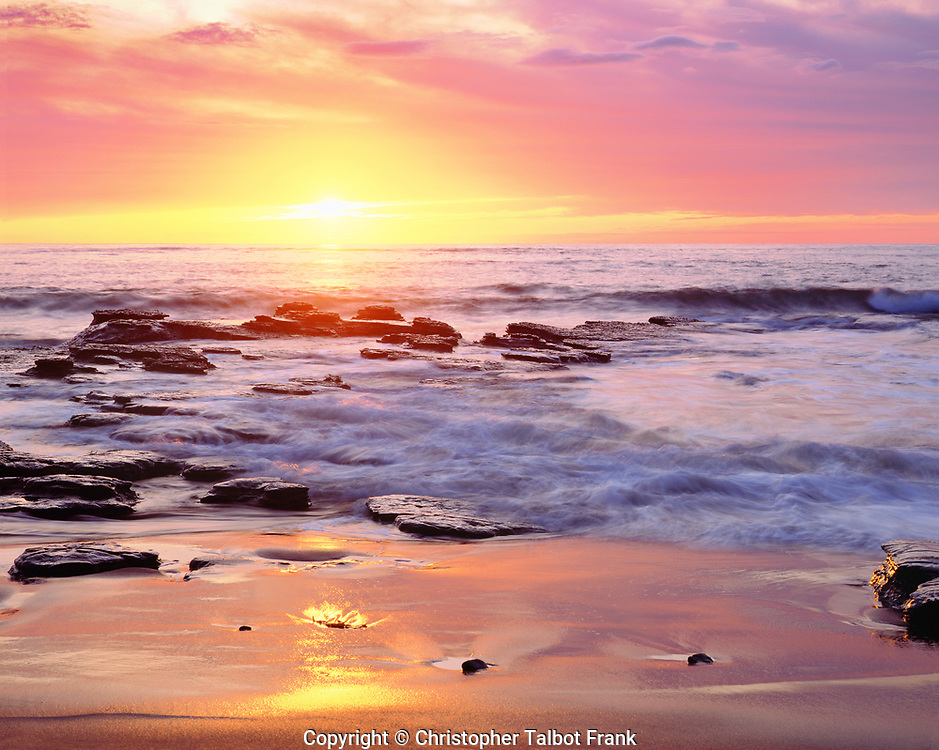 I took this photo close to 40 years ago with my 4x5 view camera of the sunset over a rocky beach in San Diego.  This beautiful yellow sunset is surround by pink clouds which reflect onto the beach.