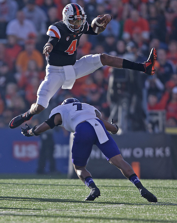 Oregon State quarterback Seth Collins jumps over Weber State's Josh Burton during the Beavers' 26-7 victory in the 2015 season opener in Reser Stadium, in Corvallis, on Friday, Sept. 4, 2015.