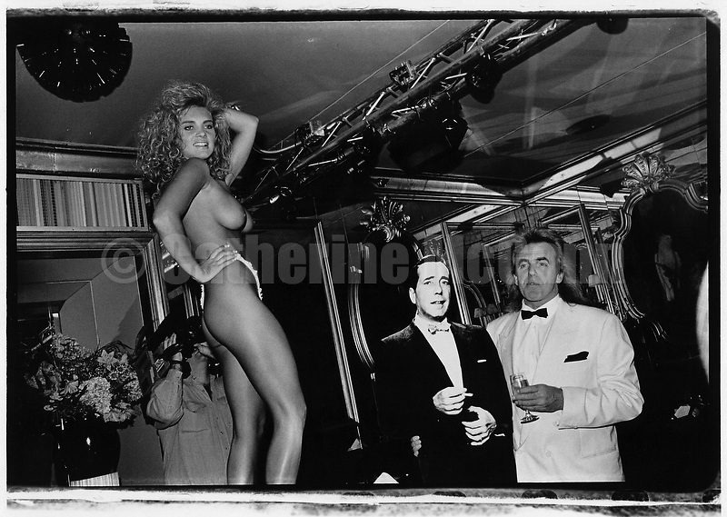 October 1992:  A stripper at the Doll House strip club owned by Peter Stringfellow (right, next to Humphrey Bogart cut out) strikes a pose for the camera.