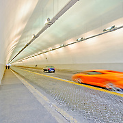 An orange supercar speeds by on the cobblestone rode of an underground tunnel in Rome, Italy.