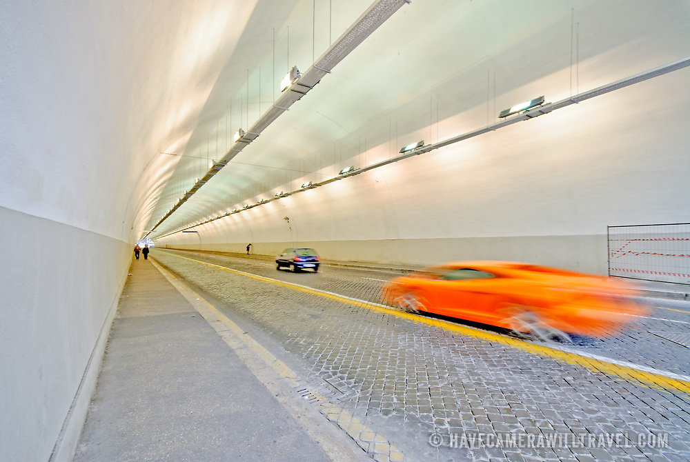 ROME, Italy - An orange supercar speeds by on the cobblestone rode of an underground tunnel in Rome, Italy.