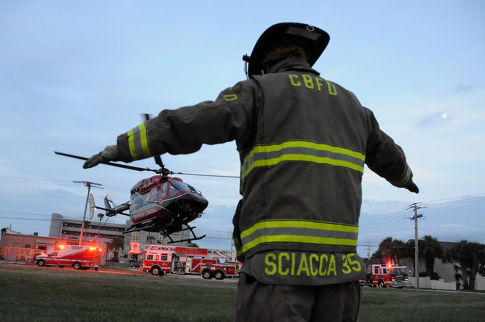 Andrew Knapp, FLORIDA TODAY -- Aug. 10, 2011 -- Firefighter-paramedic Marc Sciacca of the Cocoa Beach Fire Department signals a helicopter from Orlando Regional Medical Center to take off Wednesday night after a man was critically injured when he fell from a second-floor apartment balcony.