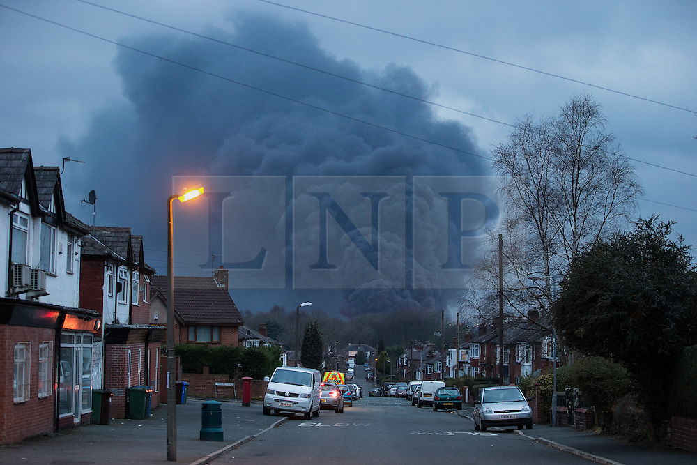 """© Licensed to London News Pictures . 15/03/2015 . Salford , UK . A large plume of smoke seen rising from the scene . Roads are closed and people have been evacuated as a large fire burns at a unit within """" Junction Eco-Park """" in Clifton , Greater Manchester , this evening (Sunday 15th March 2015) . The smoke and flames can be seen for many miles . Forty fire fighters are at the scene working to control the blaze . Photo credit : Joel Goodman/LNP"""