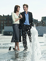 Mid-adult couple standing between water jets of fountain