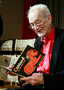 Author and illustrator Norman Bridwell holds a copy of the first Clifford the Big Red Dog book he wrote nearly 50 years ago. In support of Scholastic's global literacy campaign, Bridwell joined 11 other children's illustrators at Scholastic's New York City headquarters for the launch of a month-long online charity auction of their original artwork to benefit literacy organizations, New York, Thursday, May 5, 2011. (Stuart Ramson for Scholastic)