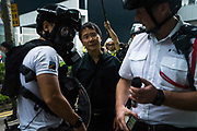A protester's microphone is confiscated by a policeman as he tries to confront the riot police in front of the Central Government Offices, during a protest against a proposed extradition law in Hong Kong, SAR China, on Wednesday, June 12, 2019. Hong Kong's legislative chief postponed the debate on legislation that would allow extraditions to China after thousands of protesters converged outside the chamber demanding the government to withdraw the bill. Photo by Suzanne Lee/PANOS