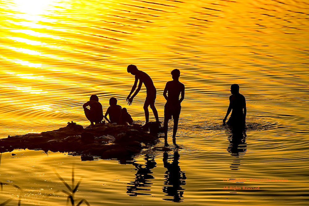 Silhouetted Bathing: Boys are silhouetted in the setting sunlight as they bath in the golden waters of the Irrawaddy River, New Bagan Myanmar.