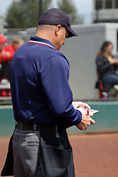22 April 2017:  Homeplate umpire Sergio Villarreal notes a pitcher change in his notebook during a Missouri Valley Conference (MVC) women's softball game between the Missouri State Bears and the Illinois State Redbirds on Marian Kneer Field in Normal IL