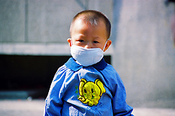 China, Taiyuan, 2008. A three-year old wearing a protective mask during China's SARS outbreak of 2003. Taiyuan was second only to Beijing in the number of infections.