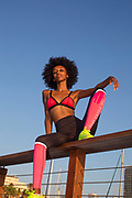 happy young african woman stretching and warming up before an outdoor workout. with a beautiful blue sky background