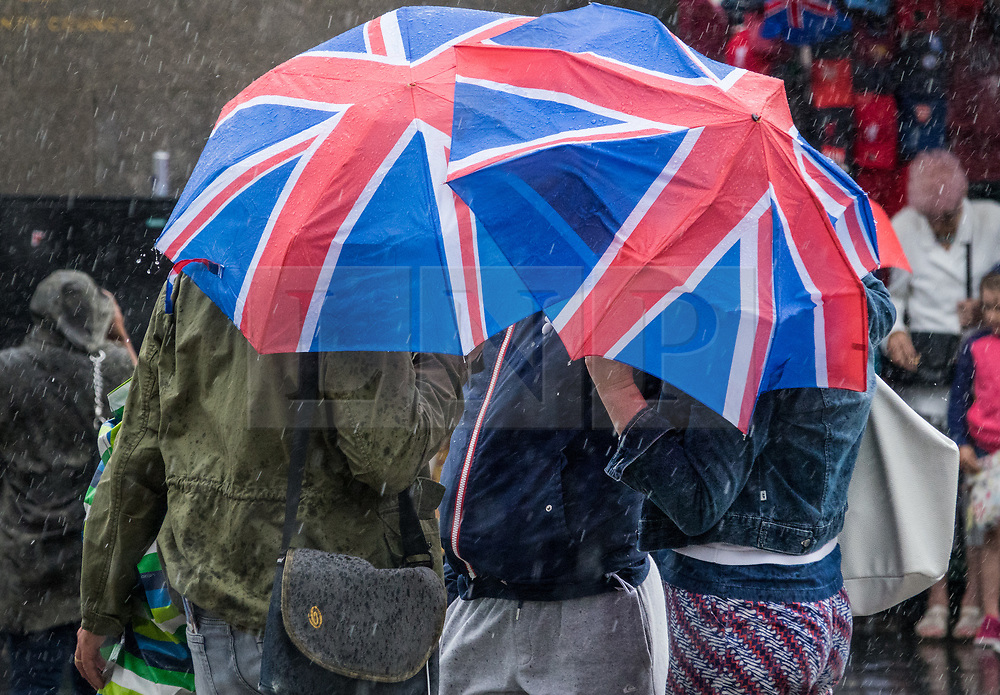 © Licensed to London News Pictures. 18/08/2017. London, UK. Tourists near Parliament shelter under Union flag umbrellas as a sudden burst of heavy rain hits central London. Today's weather has been a mixture of sunshine and showers for most of the UK. Photo credit: Peter Macdiarmid/LNP