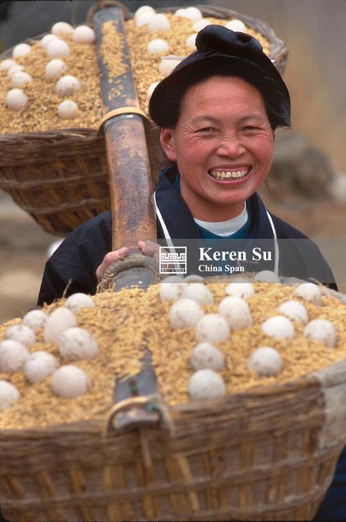 A Miao woman carrying baskets of eggs on shoulder pole, Kaili, Guizhou Province, China