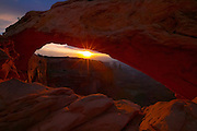 The early morning sun shines through Mesa Arch, a natural sandstone arch located in Canyonlands National Park, Utah. Washer Woman Arch is visible in the background, near the center of the image.