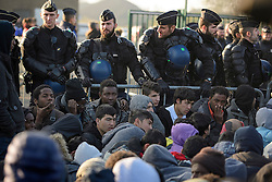 © Licensed to London News Pictures. 25/10/2016. Calais, France.  Hundreds of young, unaccompanied migrants, hoping to go to the UK, are forced by police to sit down in a confined space, as they wait to be processed to leave the migrant camp in Calais, known as the 'Jungle'. French authorities have moved thousands of refugees and migrants living at the makeshift living area on the French coast, with some still refusing to leave. . Photo credit: Ben Cawthra/LNP