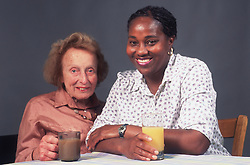 Carer sitting at table with elderly woman smiling,