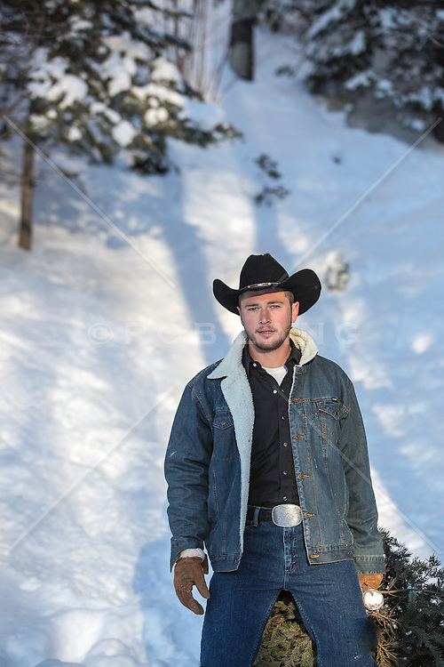 cowboy in the snow with a fresh cut tree