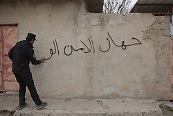 Licensed to London News Pictures. 13/02/2017. Mosul, Iraq. An officer of the Iraqi National Security Service spray paints the name of his agency on the wall of a home in east Mosul to show they have investigated the property. The house was home to an ISIS fighter and his family from Tikrit who fled the area leaving behind two victim operated explosive devices.<br /> <br /> The Jihaz Al-Amin Al-Watani, roughly translated as the National Security Service or NSS, are a secretive Iraqi agency that works under the responsibility of the Ministry of Interior. Since the liberation of eastern Mosul in January 2017 the NSS have been actively hunting down ISIS members who stayed behind to continue terrorism as part of sleeper cells and residents who worked with the group during its two year occupation. Recruiting from across the country agency is responsible for internal security inside Iraq and has a broad remit to investigate and arrest everything from terrorists and foreign spies to financial criminals and drug traffickers. Photo credit: Matt Cetti-Roberts/LNP