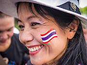 "09 JUNE 2013 - BANGKOK, THAILAND:  A woman with a Thai flag decal on her cheek participates in the White Mask anti-government protest in Bangkok. The White Mask protesters wear the Guy Fawkes mask popularized by the movie ""V for Vendetta"" and the protest groups Anonymous and Occupy. Several hundred members of the White Mask movement gathered on the plaza in front of Central World, a large shopping complex at the Ratchaprasong Intersection in Bangkok, to protest against the government of Thai Prime Minister Yingluck Shinawatra. They say that her government is corrupt and is a ""puppet"" of ousted (and exiled) former PM Thaksin Shinawatra. Thaksin is Yingluck's brother. She was elected in 2011 when her brother endorsed her.    PHOTO BY JACK KURTZ"