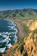 Green hills in spring and coastal waves breaking on sand shore of Christy Beach, Santa Cruz Island, Channel Islands, California