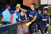 AFC Wimbledon goalkeeper Nicola Tzanev (13) high fiving and touching arms with member of the crowd during the EFL Sky Bet League 1 match between AFC Wimbledon and Shrewsbury Town at the Cherry Red Records Stadium, Kingston, England on 14 September 2019.