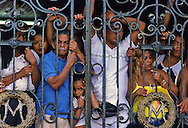 Viewers stand behind a gate to observe the parade avoiding the throng.