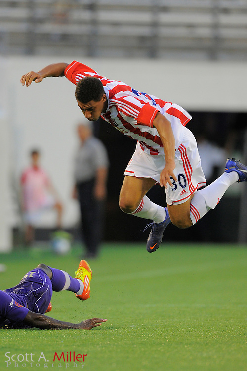 Stoke City Potters defender Ryan Shotton (30) flies through the air as he is tackled by Orlando City Lions midfielder Adama Mbengue (3) during the Potters 1-0 win at the Florida Citrus Bowl on July 28, 2012 in Orlando, Florida. ..©2012 Scott A. Miller.