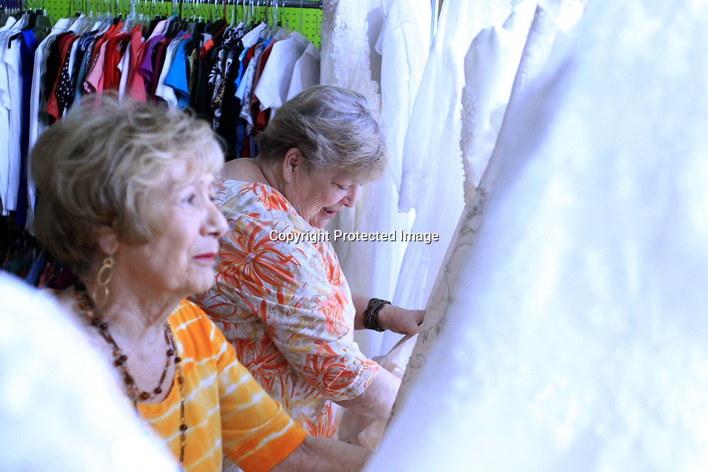 Cherie Harris and Bernie Bowles, volunteers at the Sanctuary Village Shoppe, straighten up the wedding dresses they have for sale on Thursday afternoon in Tupelo. The thrift store that benefits the Sanctuary Hospice House gets a surprising number of wedding dresses which they sell for $50.00.