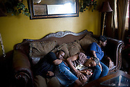 Pam Cash, 52,  catches a nap between two cleaning jobs with sons Rudy  and Nelson at home in New Orleans, LA on August 15, 2010.  Thoug very tired, things were worse five years ago after Hurricane Katrina when her adopted nephew Denzel needed heart surgery at the Superdome, she was dealing with Nelson, who has Downs Syndrome, and  Rudy, who has severe ADHD. (photo by Linda Davidson/The Washington Post)