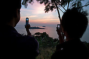 Sunset at Hat Khlong Makok. Thai tourists making souvenir snapshots with their mobile phones.