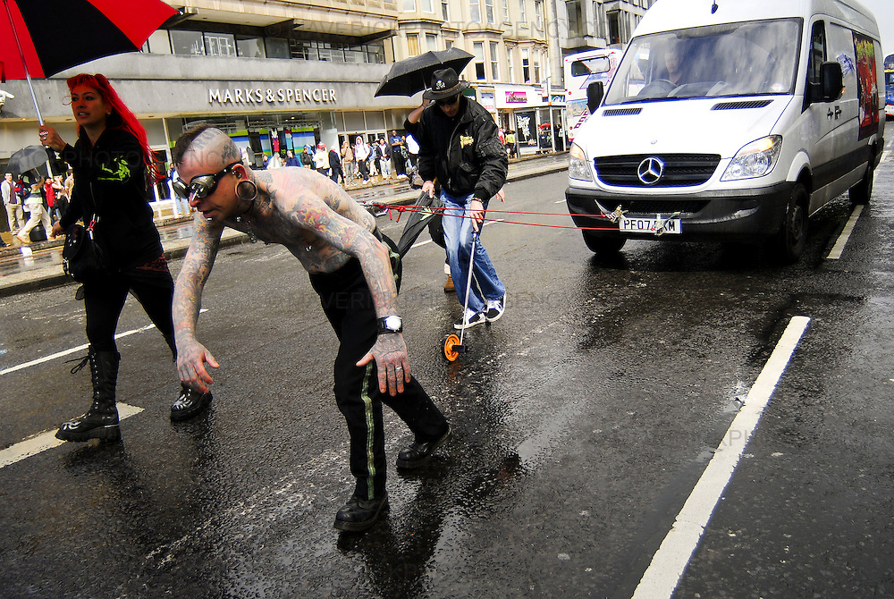 Hannibal Helmurto from the Infamous Circus of Horrors broke the Guinness World Record for pulling a 4 tonne van one hundred and seven meters along Edinburgh's Princes Street today with only two meat hooks inserted through his back. Hannibal used to work as a tax inspector in Germany and after seeing the Circus of Horrors, knew he had to join it.  Before he joined he had no tattoo's or piercing but now, 10 years on, his body is completely covered in over two hundred tattoo's, has giant yo yos fitted inside his earlobes and had his toung sliced with a laser to ensure it is forever forked.
