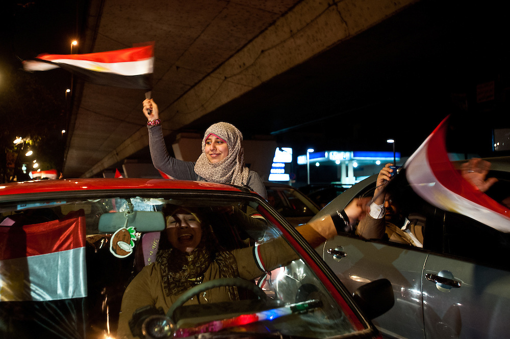 An Egyptian family drives underneath the Twenty-sixth of July Bridge in the Zamalek neighborhood of Cairo after leaving Tahrir Square, where thousands of Egyptians were celebrating the news of President Hosni Mubarak's resignation following nineteen days of protests.