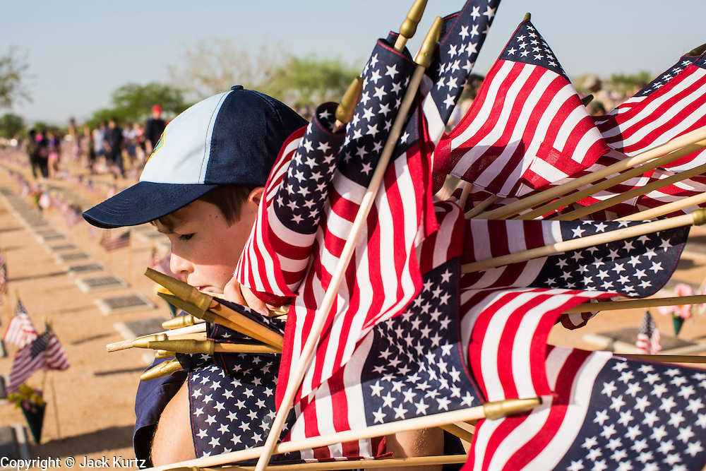26 MAY 2012 - PHOENIX, AZ:  A Cub Scout carries American flags through the National Memorial Cemetery in Phoenix, AZ, Saturday. Hundreds of Boy and Girl Scouts along with the Young Marines, a Scout like organization, place American flags on veterans' graves in the National Memorial Cemetery in Phoenix every year on the Saturday before Memorial Day.    PHOTO BY JACK KURTZ