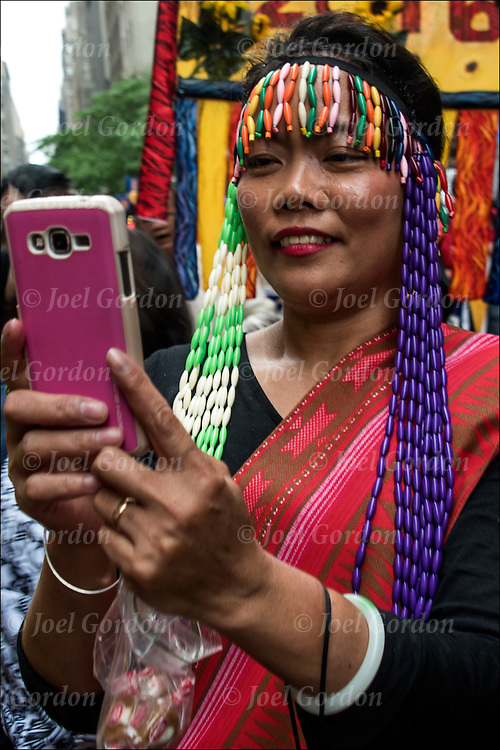 She is wearing Carnival regalia and taking a selfie.  She is one of the many faces in the Philippine Independence Day Parade in NYC.
