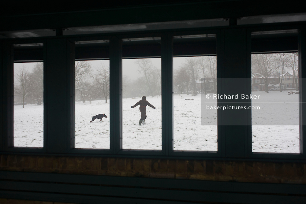 A pet dog owner plays with their doberman in their local park. From the park shelter is a scene of bleak mid-winter during a prolonged cold spell of bad weather when snow fell continuously on the capital days before, allowing families the chance to enjoy the bleak conditions in Ruskin Park in the borough of Lambeth.