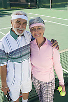 Senior couple at tennis court, portrait
