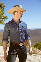 handsome cowboy on a mountain top looking off