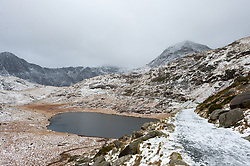 © Licensed to London News Pictures. 17/01/2018. Snowdonia National Park, Gwynedd, Wales, UK. Mount Snowdon is shrouded in cloud. Strong winds and hailstorms hit Snowdonia National Park last night. At the summit of Mount Snowdon the wind is forecast to be 50 mph with a feels-like temperature of minus 16 degrees centigrade. Photo credit: Graham M. Lawrence/LNP