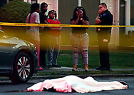 Family and friends look on as the covered body of Devon Brown lies in the street after an altercation between two children at a Kindergarten Graduation erupted in to gunfire leaving one of the childrens fathers on the run and another man dead on May 31, 2017 in Hanover Township, PA.