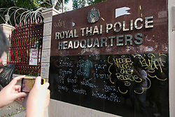 © Licensed to London News Pictures. 05/01/2014. An Anti-Government takes a photo on his smart phone of the Anti-Government graffiti written on the walls of the Royal Thai Police Headquarters during the third day of the 'Bangkok Shutdown' as anti-government protesters continue with their 'shutdown' of Bangkok.  Major intersections in the heart of the city have been blocked in their campaign to oust Prime Minister Yingluck Shinawatra and her government in Bangkok, Thailand. Photo credit : Asanka Brendon Ratnayake/LNP
