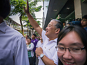 16 JANUARY 2013 - BANGKOK, THAILAND:  SUKHUMBHAND PARIBATRA, candidate for Governor of Bangkok, waves to voters on Silom Road in Bangkok. The Oxford educated Sukhumbhand is a member of the Thai royal family (he is a great grandson of the late Thai King Chulalongkorn). He is a member of the Thai Democrat party and was first elected Governor of Bangkok in 2009. He is running for reelection this year. Sukhumbhand faces six challengers in the March 3 election. His toughest opponent is expected to be Police General Pongsapat Pongcharoen, who is running under the banner of the Pheu Thai Party, which controls the Prime Minister's office and Parliament.    PHOTO BY JACK KURTZ