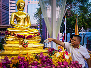 13 APRIL 2018 - BANGKOK, THAILAND:  A man pours water on a Buddha statue to make merit during the first day of Songkran in Lumpini Park in Bangkok. Songkran is the traditional Thai New Year celebration best known for water fights.   PHOTO BY JACK KURTZ