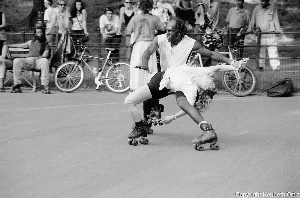 Two roller skaters in central park on a sunny summer day.