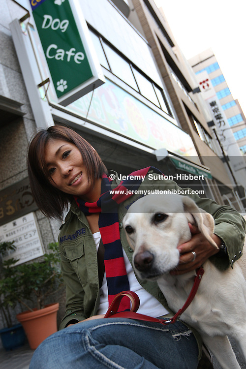 """Saori 'Aya' Soejima, aged 31, walking a dog,called  'Rolo' (aged 3.5yrs),  that she rents by the hour from 'Dog and Cafe Bar Janet Village"""", in Gotanda district,  Tokyo, Japan, Thursday, Nov. 8th, 2007. Saori Soejima has rented Rolo the labrador more than 40 times, and as a Gold Card Member of the rental shop she pays Japanese Yen ¥1,600 per hour, as opposed the usual price (for non-gold members) of ¥2,100 per hour."""