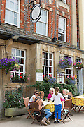 Diners family group at The Bull medieval inn old gastro pub hotel in Burford High Street in The Cotswolds, Oxfordshire, UK