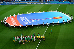 Players shake hands with one another as a huge Women's World Cup banner is carried on to the pitch prior to the beginning of the match