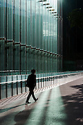 Silhouette of a salaryman walking by the glass front of a tall office building in Shiodome, Shimbashi, Tokyo, Japan. Monday November 28th 2016