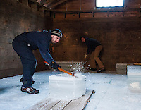 Derek Goldstone and Alex Chelstowski work in unison packing slabs of ice into the Rockywold Ice House during the annual Ice Harvest on Tuesday afternoon.  (Karen Bobotas/for the Laconia Daily Sun)